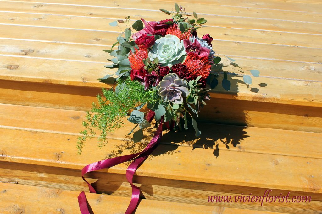 Burgundy rustic bouquet with succuelents, proteas, cymbidiums and eucalyptus